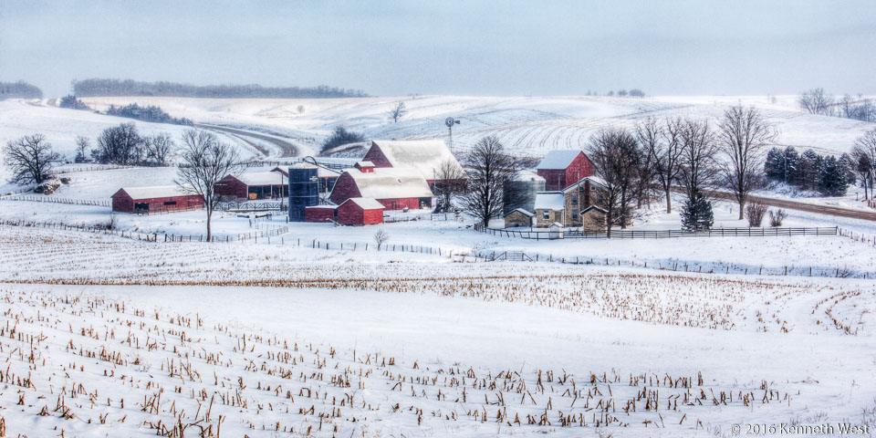 Heartland Winter - GW-015-W - I made this photograph on the Grant Wood Scenic Byway in December. The wind chill was below zero. If you look closely you will see a white speckled appearance, particularly on the red barns – this effect was due to a strong wind blowing the soft powdered snow. - Wide 1 x 2 Proportion
