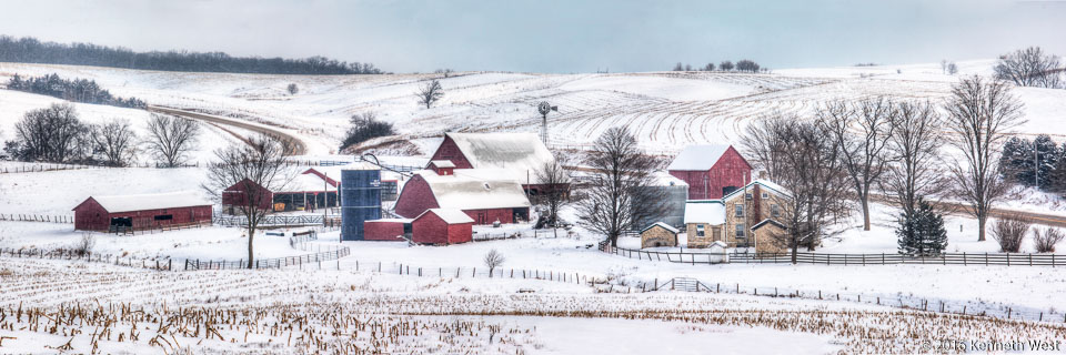 Heartland Winter - GW-054-P - I made this photograph on the Grant Wood Scenic Byway in December. The wind chill was below zero. If you look closely you will see a white speckled appearance, particularly on the red barns – this effect was due to a strong wind blowing the soft powdered snow. - Panorama 1 x  3 Proportion